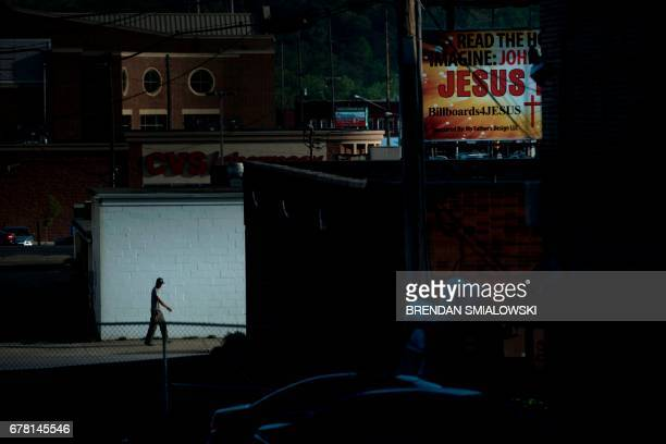 Man walks down an ally near a billboard for Jesus on April 20, 2017 in Huntington, West Virginia. - Huntington, the city in the northwest corner of...