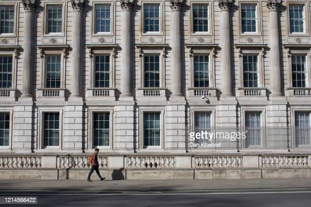 Man walks down an otherwise empty Whitehall on March 24, 2020 in London, England. British Prime Minister, Boris Johnson, announced strict lockdown...