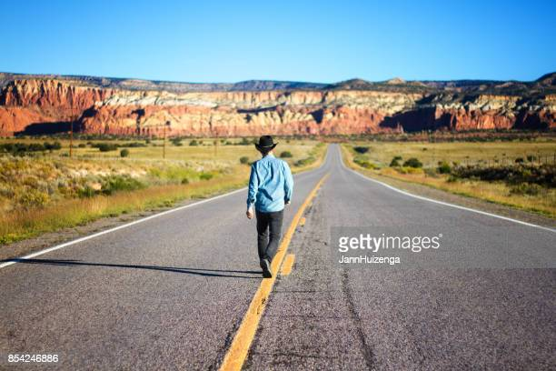 man walks down center of beautiful empty western highway - mid section stock photos and pictures