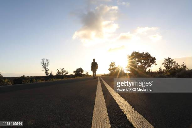 man walks down centre line of highway into the sunset - one man only stock pictures, royalty-free photos & images