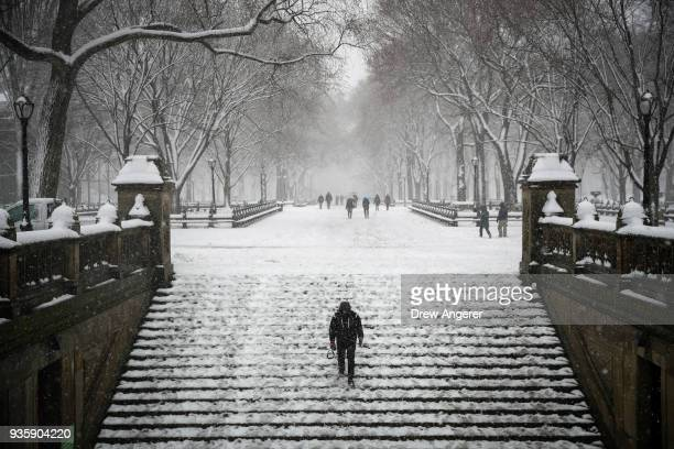 A man walks down steps toward the Bethesda Fountain and Terrace in Central Park during a snowstorm March 21 2018 in New York City The fourth...