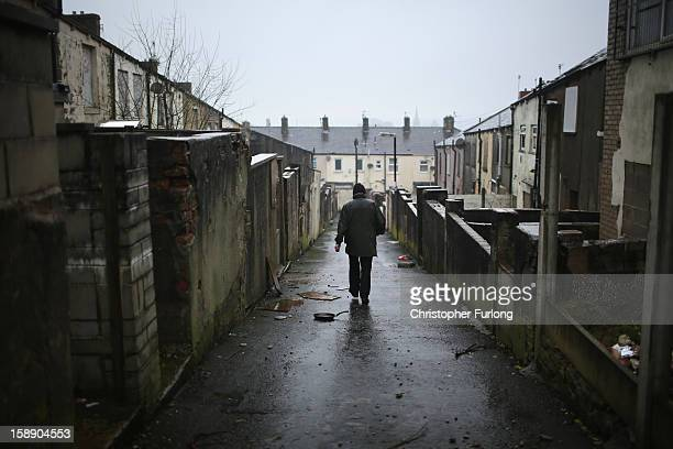 A man walks down the alleyway at the back of former council houses a street in the Lancashire town of Accrington as they wait to be modernised by...