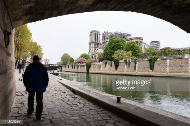 A man walks down the 'L'Archeveche' bridge and looks at the damage caused to NotreDame Cathedral following a major fire yesterday on April 16 2019 in...