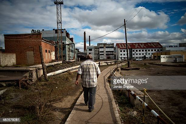 Man walks down the road that leads to the Mongolian Sharyn Gol coal mine located in the Sharyngol district. Mongolia today is known for its large...