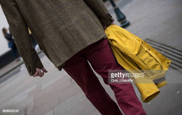 A man walks down the road wearing a tweed jacket red torusers and holding a yellow jacket in British Prime Minister Theresa May's constituency of...