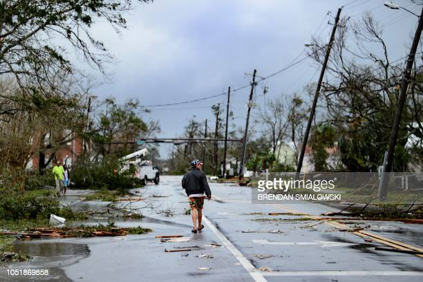 TOPSHOT A man walks down the street after Hurricane Michael made landfall on October 10 2018 in Panama City Florida Michael slammed into the Florida...