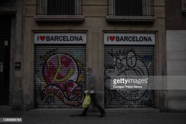 Man walks down the street besides a souvenir store in Barcelona, on November 16, 2020 in Barcelona, Spain. International tourism plummeted this...