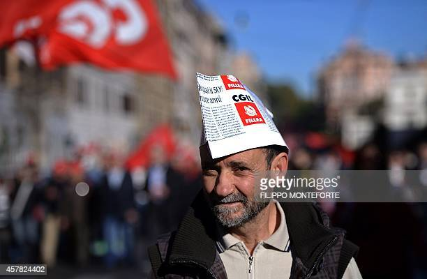 A man walks during a demonstration organised by Italian General Confederation of Labour union on October 25 2014 in central Rome as part of a...