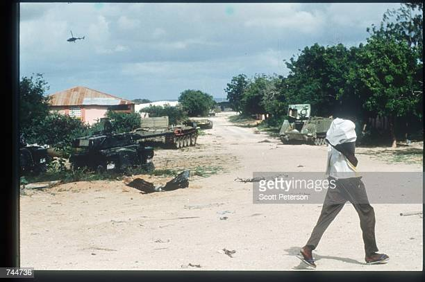 A man walks during a helicopter attack December 6 1993 in Mogadishu Somalia US gunships attacked the compound of warlord Mohammad Aidid in response...