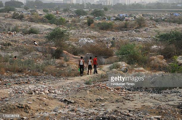 A man walks during dawn in a vacant land which is used by the people to dump garbage on the ocassion of World Environment Day on June 5 2013 in Noida...