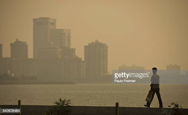 A man walks during the sunset with the cityscape on the background in Mumbai Maharastra India