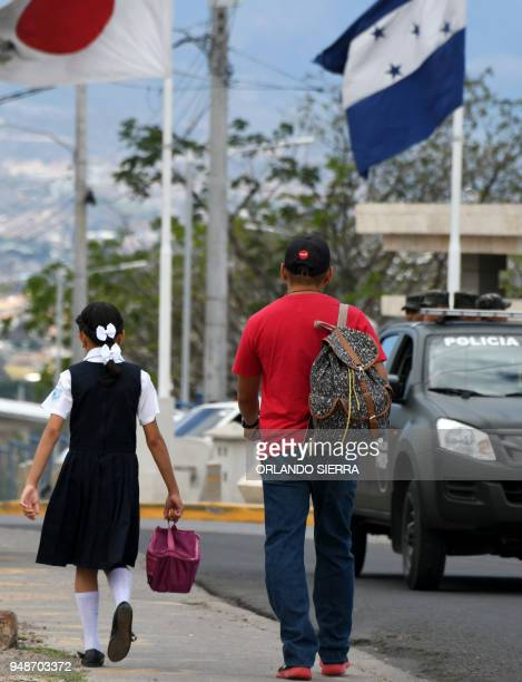 A man walks her daughter to school in Tegucigalpa on April 18 2018 Students are also victims of the prevailing insecurity in Honduras where the...