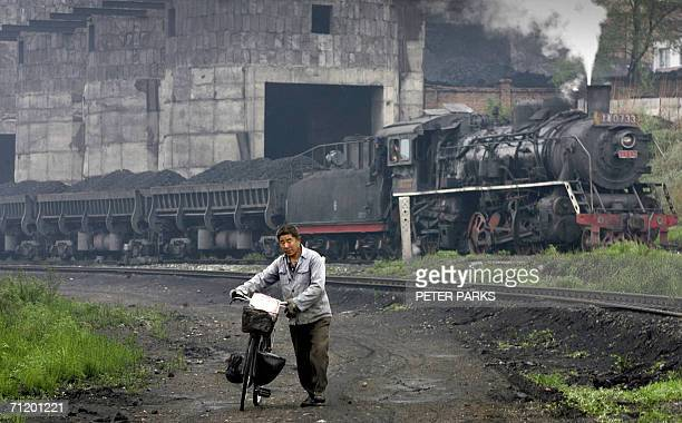 A man walks his bicycle as a steam train leaves the Beichang coal washery in Jixi in northeast China's Heilongjiang province 02 June 2006 China is...
