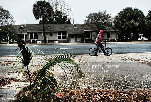 A man walks his bicycle in a struggling neighborhood in Pensacola on December 4 2016 in Pensacola Florida Pensacola along with much of the Panhandle...