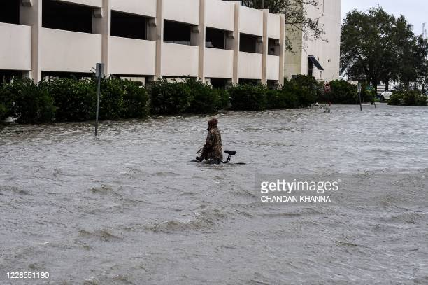 TOPSHOT A man walks his bicycle through a street flooded by Hurricane Sally in Pensacola Florida on September 16 2020 Hurricane Sally barrelled into...