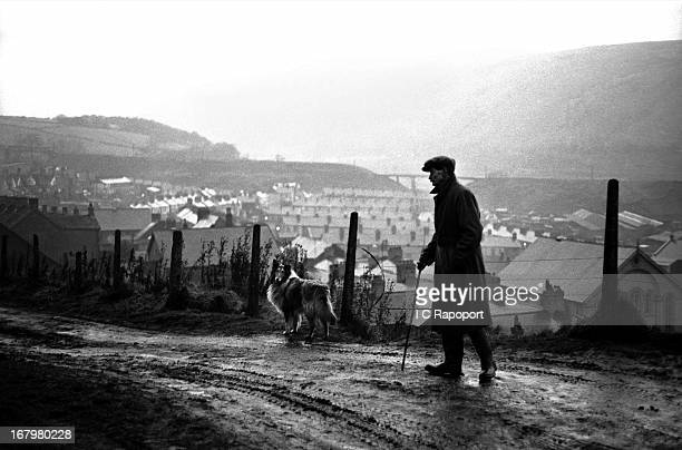 Man walks his Collie dog on a dirt path overlooking a Welsh mining town in1966 in a mining town in South Wales