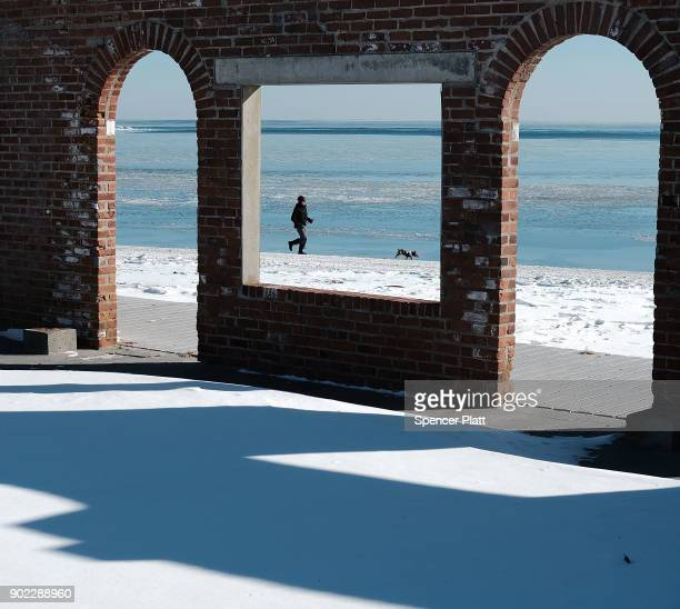 A man walks his dog along a beach covered in snow and ice as temperatures continue to stay below freezing in much of the Northeast on January 7 2018...