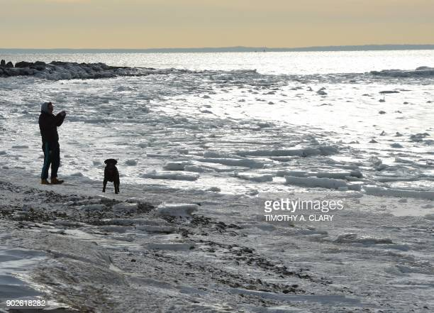 A man walks his dog along the frozen Long Island Sound at Compo Beach in Westport Connecticut January 8 2018 The northeast is still facing record low...
