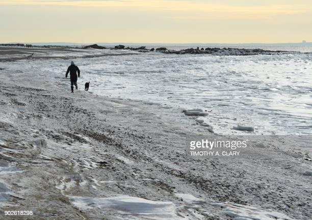 TOPSHOT A man walks his dog along the frozen Long Island Sound at Compo Beach in Westport Connecticut January 8 2018 The northeast is still facing...