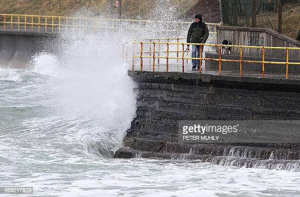 A man walks his dog along the the coastal path as waves break along the shore in Portrush Northern Ireland on December 24 2013 A man and a woman died...