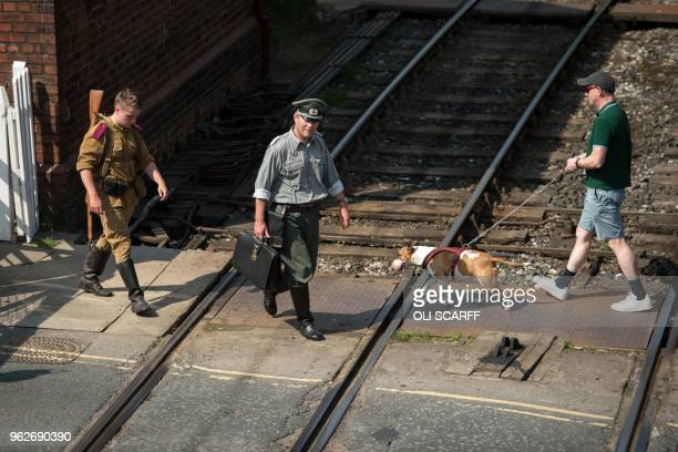 Man walks his dog among people dressed in costumes of the 1940s attending a reenactment-themed weekend event held along the East Lancashire Railway's...