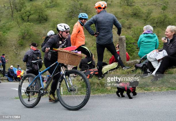 A man walks his dog and bike up the Cote de Park Rash ascent near the village of Kettlewell in the Yorkshire Dales ahead of the arrival of the...