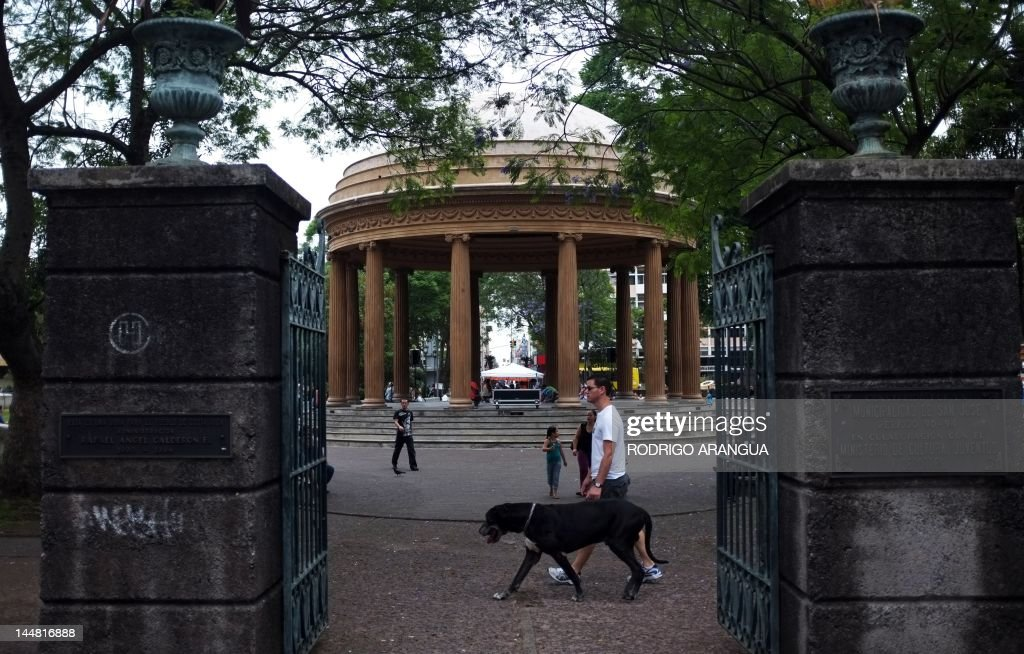 A man walks his dog at Morazan square in San Jose, on May 19, 2012