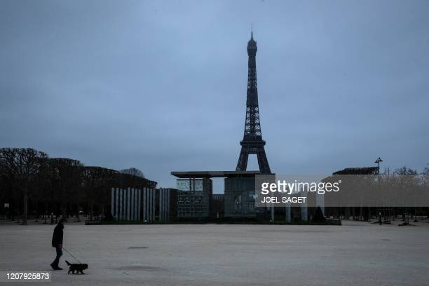 TOPSHOT A man walks his dog at the Champs de mars on March 21 2020 in Paris as a strict lockdown comes into in effect in France to stop the spread of...