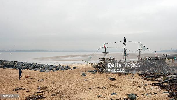 A man walks his dog by the Black Pearl driftwood pirate ship on the beach of the River Mersey at New Brighton in north west England on January 19...
