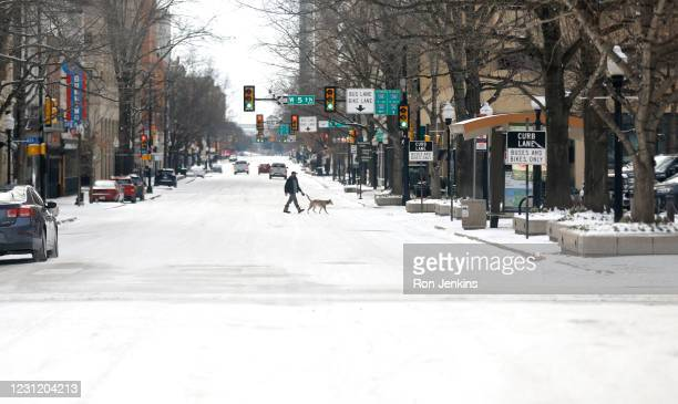 Man walks his dog downtown after a snow storm on February 16, 2021 in Fort Worth, Texas. Winter storm Uri has brought historic cold weather and power...