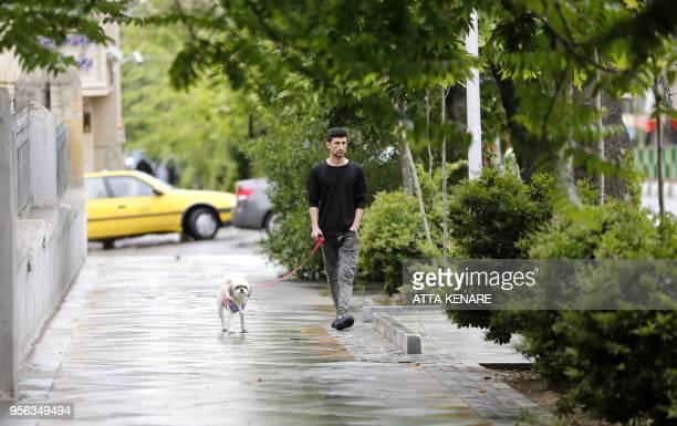 A man walks his dog in Tehran on May 9 2018