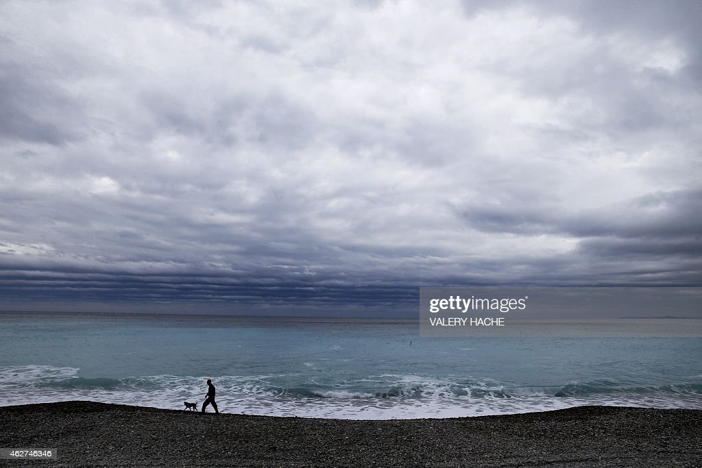 A man walks his dog on a beach of the mediterranean sea in Nice, southeastern France, on February 4, 2015.