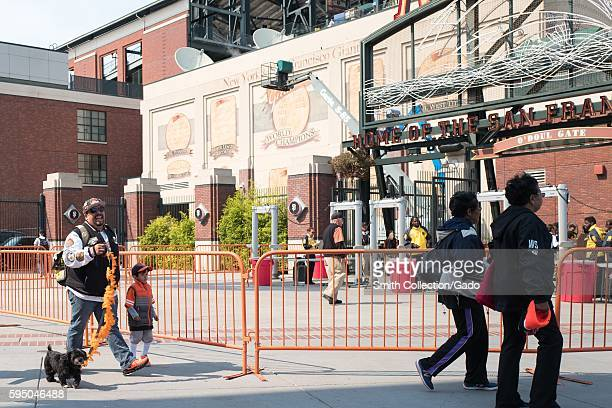 A man walks his dog on a leash decorated with the colors of the Giants towards O'Doul Gate before the Dog Days of Summer promotional baseball game a...