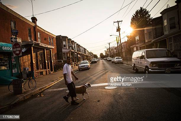 Man walks his dog on August 20, 2013 in the Whitman Park neighborhood of Camden, New Jersey. The town of Camden, which was once a large industrial...