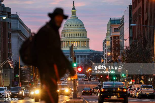 Man walks his dog on north capitol street as the sun rises over the US Capitol on December 28, 2020 in Washington, DC. President Donald Trump signed...