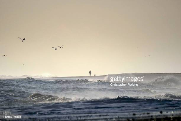 Man walks his dog on the beach as waves break on to the beach and and sand dunes in the village of Hemsby on November 06, 2019 in Great Yarmouth,...