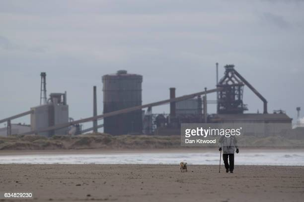 A man walks his dog on the beach in front of the former SSI Steel making plant on February 8 2017 in Redcar United Kingdom The SSI steel making plant...