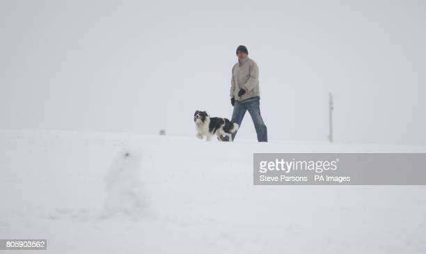 A man walks his dog on the snow covered Dunstable Downs in Bedfordshire