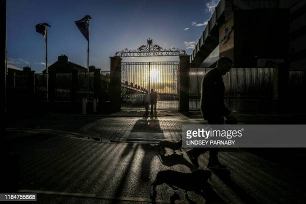 TOPSHOT A man walks his dog outside Anfield stadium in Liverpool north west England on November 26 on the eve of Liverpool's UEFA Champions League...