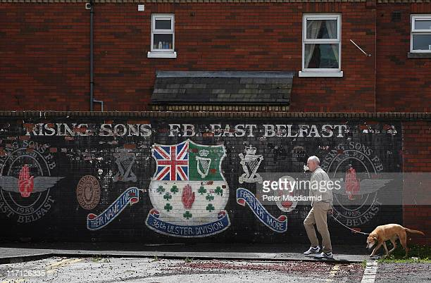 A man walks his dog past a faded mural in the mainly protestant area of East Belfast on June 23 2011 in Northern Ireland The Short Strand and...