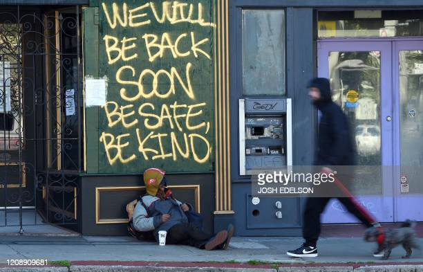 Man walks his dog past a homeless man sleeping under a message painted on a boarded up shop in San Francisco, California on April 2020, during the...
