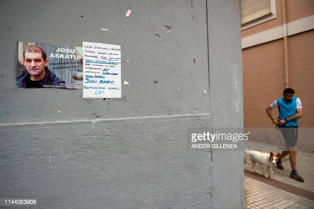 Man walks his dog past a poster calling for the release of one of the most influential leaders of former Basque separatist group ETA, Jose Antonio...