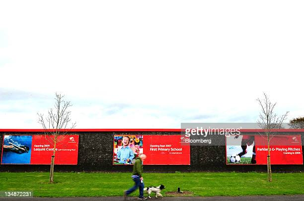 A man walks his dog past advertising boards for a community development at Adamstown Central a mixeduse construction site in Dublin Ireland on...