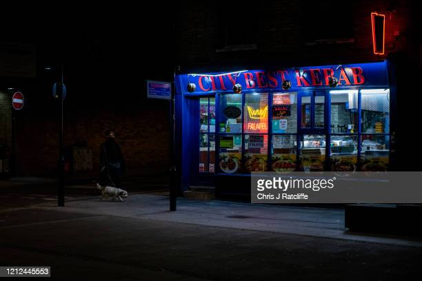 Man walks his dog past an open kebab takeaway restaurant at night time in Shoreditch on May 9, 2020 in London, England. The UK is continuing with...