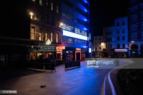 A man walks his dog through a deserted Leicester Square at what would usually be a busy period of Friday night revelry on March 20 2020 in London...