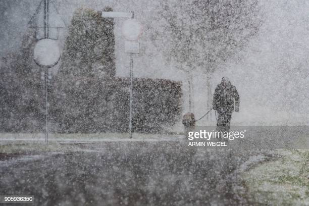 TOPSHOT A man walks his dog through heavy snowfall in Straubing southern Germany on January 17 2018 / AFP PHOTO / dpa / Armin Weigel / Germany OUT