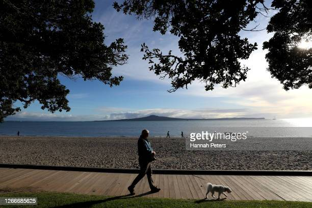 Man walks his dog under level 3 restrictions along Kohimarama Beach on August 17, 2020 in Auckland, New Zealand. COVID-19 restrictions are in place...