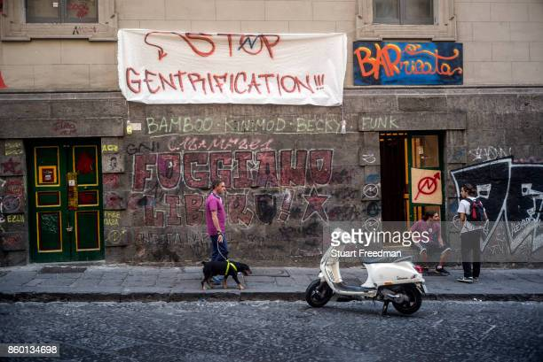 A man walks his dogs past students protesting gentrification in Naples Italy The city long dilapidated now has areas that are expensive for locals...