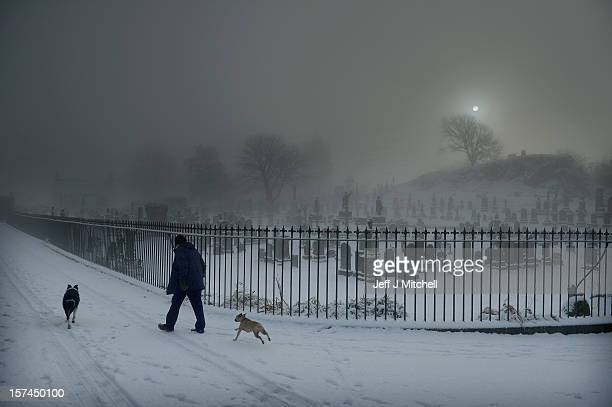 A man walks his two dogs past Stirling Castle graveyard on December 3 2012 in Stirling Scotland Snow and sleet has hit many parts of Scotland with...