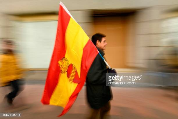 A man walks holding a Spanish flag with the Sacred Heart used by Carlism movement during demonstration called by the farright party VOX against...